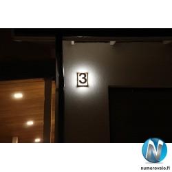 Numero 3 rapatulla vaalealla seinällä